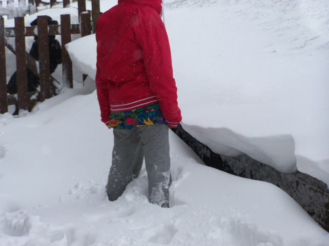 Daughter up her knees in snow