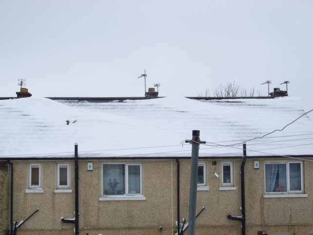 Snow difting across the roofs